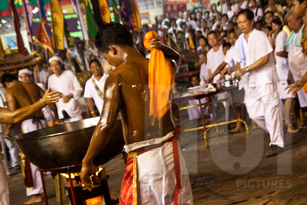 A mah-song bathes in boiling hot oil during the Phuket Vegetarian Festival, Phuket, Thailand.