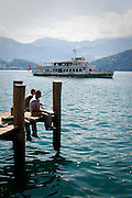 A paddlewheel steamboat cruise arrives in Weggis — a small town on Lake Lucerne, Switzerland — while fishermen fish from the dock.