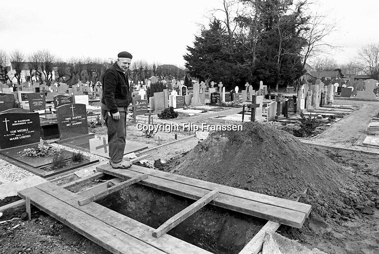 Nederland, Wijchen, 15-5-1986 een grafdelver , hovenier van het kerkhof, heeft een graf klaargemaakt . Zometeen kan de begrafenisondernemer de kist met de overledene in het gat laten zakken .Foto: Flip Franssen
