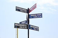 04 June 2016: A street sign in the ballpark shows the distance to each of the eight competing schools. The Nova Southeastern University Sharks played the Millersville University Marauders in Game 14 of the 2016 NCAA Division II College World Series  at Coleman Field at the USA Baseball National Training Complex in Cary, North Carolina. Nova Southeastern won the game 8-6 and clinched the NCAA Division II Baseball Championship.