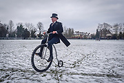 """© Licensed to London News Pictures. 18,03,2018. Surbiton, UK.  <br /> Families enjoy riding Penny Farthings in the snow in Surbiton today 18 March 2018. Locals were taking part in a project celebrating the Penny Farthing's maker, one time Surbiton resident and carpenter's apprentice John Keen, who became one of the most important pioneering figures in cycling history. He quit his carpentry career and dedicated himself to becoming the undisputed """"boneshaker"""" racing champion of Britain. He could ride half a mile in 2 min 45 secs. Keen realised the """"boneshaker"""" was heavy and cumbersome in design and went on to build something better - the """"ordinary bicycle"""" - which later became known at the """"penny farthing"""" Known as Happy Jack, Keen raced until he was 36, but his health failed and he faded into obscurity. He died in 1902.  Photo credit: Stephen Simpson/LNP"""
