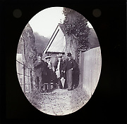 Magic lantern slide two well dressed couples one older one younger standing in alleyway in rural location  UK circa 1900