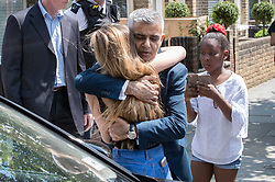 © Licensed to London News Pictures. 18/06/2017. London, UK. London Mayor Sadiq Khan hugs 12 year old resident Charlene Nolan after attending a chuch service near site of the burnt out Grenfell tower block . The blaze engulfed the 27-storey building killing dozens - with 34 people still in hospital, many of whom are in critical condition. The fire brigade say that they don't expect to find anyone else alive. Photo credit: Peter Macdiarmid/LNP