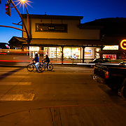 Two mountain bikers wait at the town square light after partying in Jackson, Wyoming.