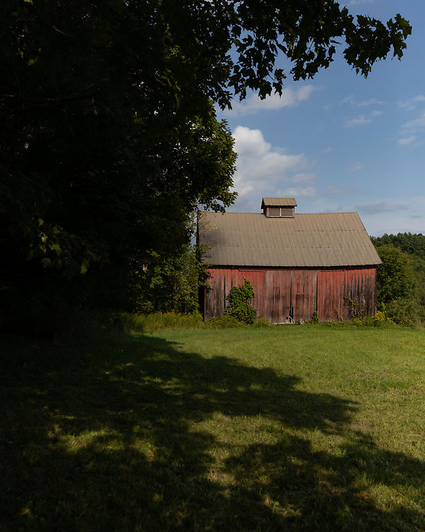 An old red barn situated atop a rolling pasture in Central Vermont.
