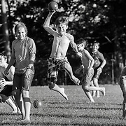 A camper jumps in the air with a ball clutched in his hand while playing a game with other campers in the boys camp area at Interlochen Center for the Arts in Interlochen, Michigan.