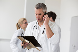 Doctor on phone with file while colleagues in background