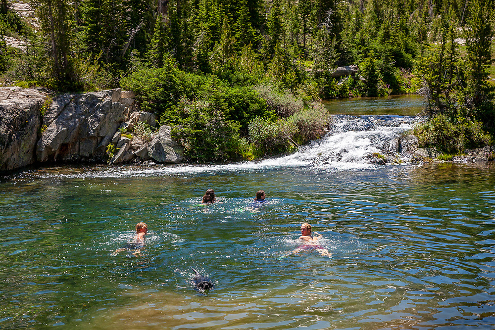 Two couples cooling off with a swim in Alice Lake with Black Labrador Retriever joining in on a beautiful summer day with El Capitan Peak in background 9902 feet / 3018 meters.  Licensing and Open Edition Prints. MR