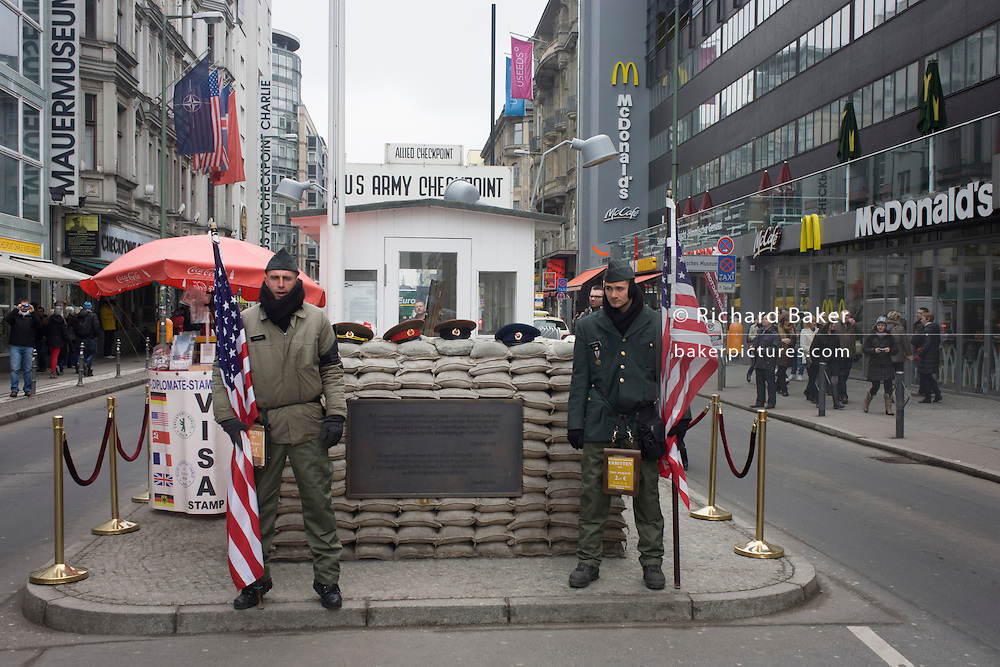 "Young men re-enact the former border crossing between Communist East and West Germany during the Cold War at the site of the former Checkpoint Charlie, the border. The Berlin Wall was a barrier constructed by the German Democratic Republic (GDR, East Germany) starting on 13 August 1961, that completely cut off (by land) West Berlin from surrounding East Germany and from East Berlin. The Eastern Bloc claimed that the wall was erected to protect its population from fascist elements conspiring to prevent the ""will of the people"" in building a socialist state in East Germany. In practice, the Wall served to prevent the massive emigration and defection that marked Germany and the communist Eastern Bloc during the post-World War II period."