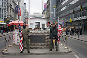 """Young men re-enact the former border crossing between Communist East and West Germany during the Cold War at the site of the former Checkpoint Charlie, the border. The Berlin Wall was a barrier constructed by the German Democratic Republic (GDR, East Germany) starting on 13 August 1961, that completely cut off (by land) West Berlin from surrounding East Germany and from East Berlin. The Eastern Bloc claimed that the wall was erected to protect its population from fascist elements conspiring to prevent the """"will of the people"""" in building a socialist state in East Germany. In practice, the Wall served to prevent the massive emigration and defection that marked Germany and the communist Eastern Bloc during the post-World War II period."""