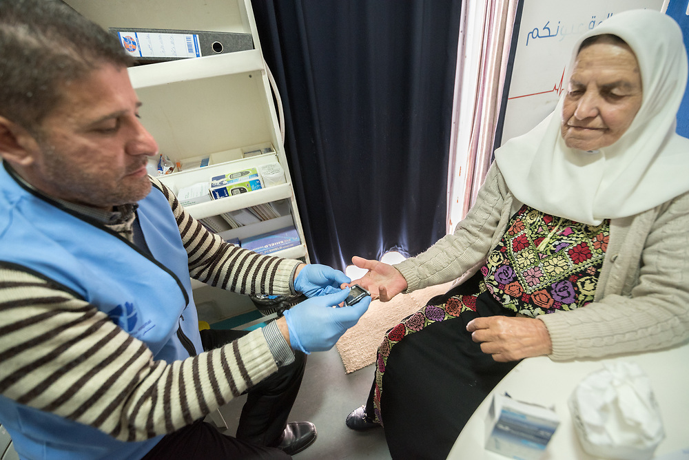 26 February 2020, Abu Dis, Palestine: 87-year-old Diabetes patient Hamama Jaffal from Abu Dis visits the Augusta Victoria Hospital's Mobile Diabetes Clinic. Here, taking a glucotest administered by supervisor Ziad Paradiah. In an effort to make Diabetes services more accessible to people in the West Bank, the Augusta Victoria Hospital offers a Mobile Diabetes Clinic, which moves around to various locations in the West Bank, offering screening and routine testing for Diabietes and the symptoms it causes.