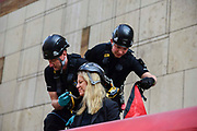 Police officers attach a harness to a climate change protesters who glued herself to the roof  of a Docklands Light Railway carriage on April 17, 2019 in London,England, United Kingdom. This is the third day of a coordinated protest by the Extinction Rebellion group who are demanding the government decisive action from the UK Government on climate change.