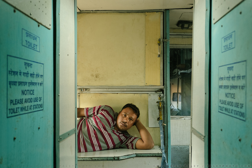 Between wagons, one of the train staff in charge of changing sheets takes a break on a hard bench.<br /> Inside the Dibrugarh-Kanyakumari Vivek Express, the longest train route in the Indian Subcontinent. It joins Kanyakumari, Tamil Nadu, which is the southernmost tip of mainland India to Dibrugarh in Assam province, near the border with Burma.