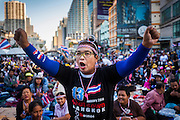 """13 JANUARY 2014 - BANGKOK, THAILAND:  An anti-government protestor cheers during a rally in the Asoke intersection in Bangkok. Tens of thousands of Thai anti-government protestors took to the streets of Bangkok Monday to shut down the Thai capitol. The protest was called """"Shutdown Bangkok"""" and is expected to last at least a week. The Shutdown Bangkok protest is a continuation of protests that started in early November. There have been shootings almost every night at different protests sites around Bangkok, including two Sunday night, but the protests Monday were peaceful. The malls in Bangkok stayed open Monday but many other businesses closed for the day and mass transit was swamped with both protestors and people who had to use mass transit because the roads were blocked.   PHOTO BY JACK KURTZ"""