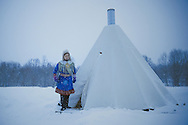 Sami woman standing near a lavvu, a temporary dwelling used by the indigenous people of northern Scandinavia.