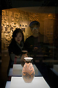 Visitors look at a vessel on display in glass case in the Shaanxi History Museum, Xian, China