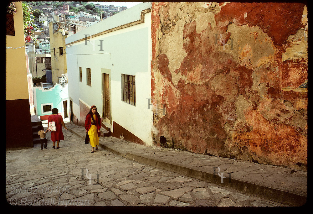 Woman in red sweater and yellow dress walks up street past old building facade; Guanajuato, Gto Mexico