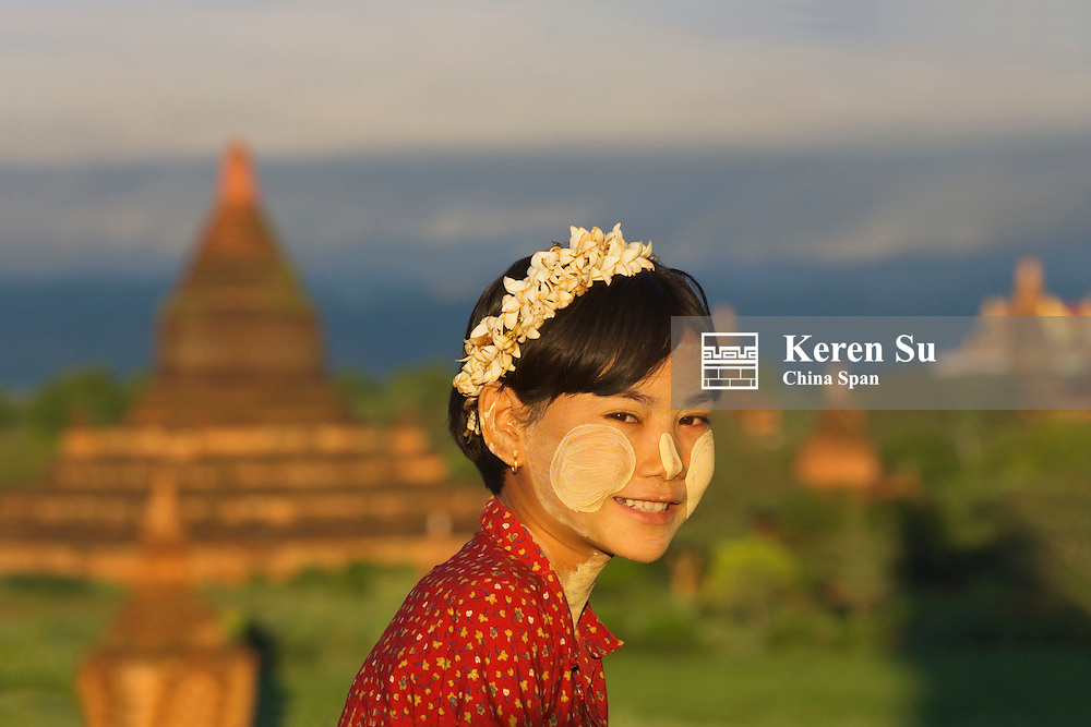 Girl face painted white with temples, Bagan, Myanmar