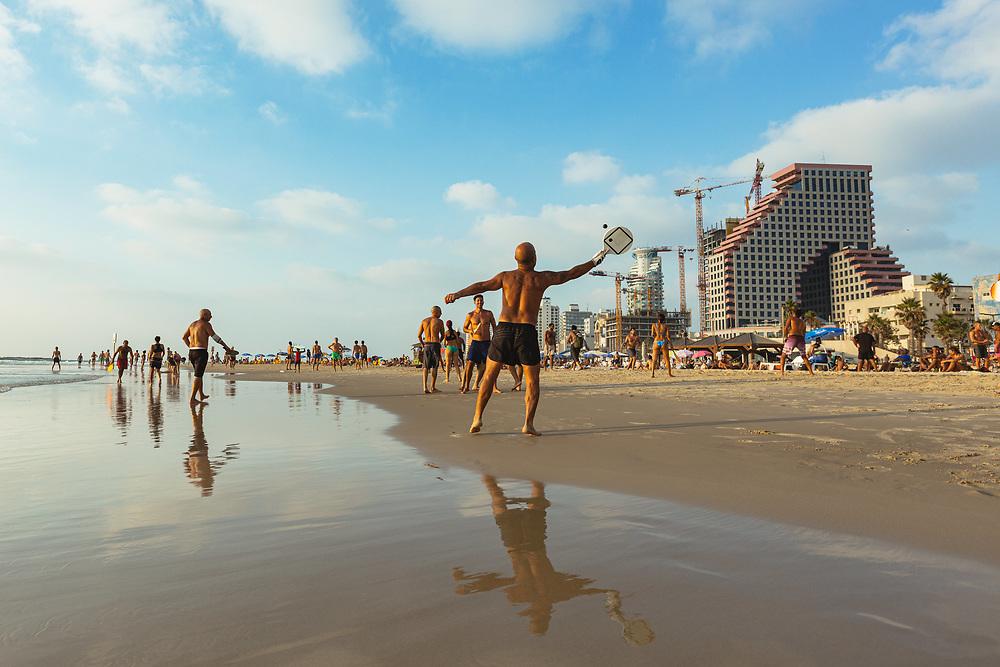 People enjoy a warm summer afternoon, playing paddleball (Matkot in Hebrew) at Frishman Beach in Tel Aviv, Israel