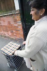 Older woman pushing a shopping trolley on her way to the shops,