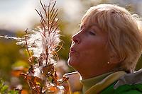 Portrait of mature woman blowing on fireweed flower seeds in Kodiak, Alaska, autumn