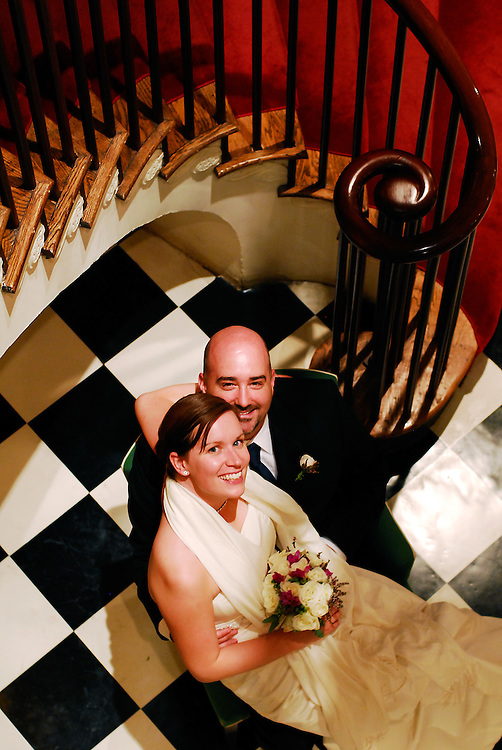 A bride and groom pose by a staircase at the Harvard Faculty Club, Cambridge, MA.