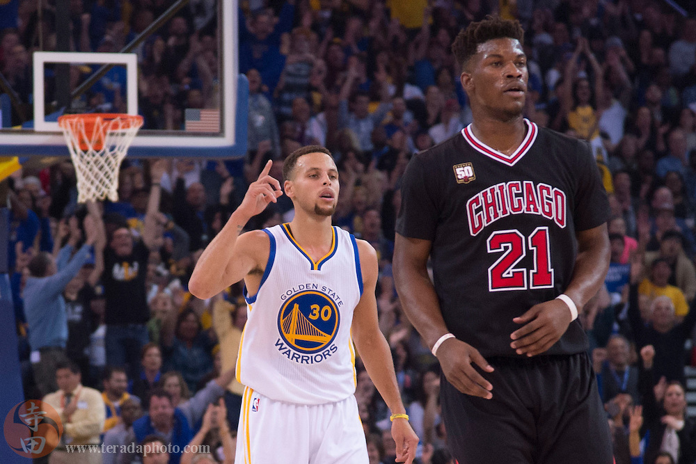 November 20, 2015; Oakland, CA, USA; Golden State Warriors guard Stephen Curry (30) celebrates after a made tree-point basket behind Chicago Bulls guard Jimmy Butler (21) during the first quarter at Oracle Arena.