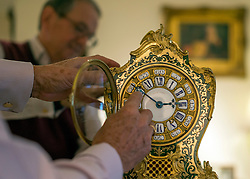 """© Licensed to London News Pictures. 23/10/2014. Guildford, UK As British Summer Time comes to an end, staff at Horological Workshops start the task of changing the 100's of clocks at their store in Guildford, Surrey, UK. Michael Tooke who has owned the store for over 40 years and worked in the clock business all his life said. """"at this time of year we get a lot of people who bring clocks in for repair after they have changed the time incorrectly by winding back the hands manually"""". Clocks change on Sunday morning 26th October. Photo credit : Stephen Simpson/LNP"""