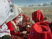 "Ikhbal (hiding under the white veil) and sister Irasia arriving at Tash Seri camp (Mustafa Qol's camp) and being welcomed with ""Borsot"" (fried dough), yoghurt and tea by the local women of Tash Seri.<br /> With Ikhbal, the recently married woman  moving for the first time to her husband's camp. She just exchanged the red veil of the unmarried girl for the white veil signifying that she is now a married woman.<br /> <br /> Trekking through the high altitude plateau of the Little Pamir mountains, where the Afghan Kyrgyz community live all year, on the borders of China, Tajikistan and Pakistan."