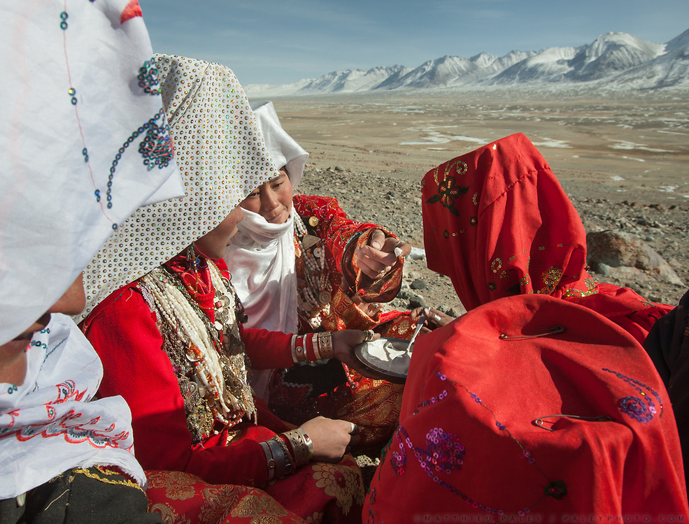 """Ikhbal (hiding under the white veil) and sister Irasia arriving at Tash Seri camp (Mustafa Qol's camp) and being welcomed with """"Borsot"""" (fried dough), yoghurt and tea by the local women of Tash Seri.<br /> With Ikhbal, the recently married woman  moving for the first time to her husband's camp. She just exchanged the red veil of the unmarried girl for the white veil signifying that she is now a married woman.<br /> <br /> Trekking through the high altitude plateau of the Little Pamir mountains, where the Afghan Kyrgyz community live all year, on the borders of China, Tajikistan and Pakistan."""