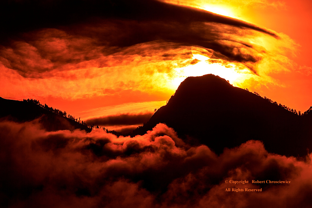 Fiery Volcanic Sunset:  With the billowing cloud bank below and a thick mountain mist above, a volcanic Silhouette is cast before a fiery sky, just as the sun seemingly sets into its crater, Mentagi Lombok Indonesia.