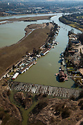Nederland, Limburg, gemeente Maastricht, 07-03-2010; waterhuishouding van de Maas. De overlaat, onder in beeld voert - bij hoogwater - extra water af om zo de stuw bij Borgharen te ontlasten. Rechts het verbindingskanaal wat leidt naar de Zuid-Willemsvaart. Het eiland Bosscherveld (l) wordt gedeeltelijk afgegraven, de Maas kan bij hoogwater in de toekomst ook over het eiland stromen. De bebouwing van Maastricht aan de horizon..Water management of the Meuse. The spillway (bottom) functions in case of high waters as an extra relieve for the weir at Borgharen. On the right the channel which leads to the South Willemsvaart. The island Bosscherveld (l) is partially excavated, in the future the Meuse high water will flow over the island..luchtfoto (toeslag), aerial photo (additional fee required).foto/photo Siebe Swart