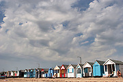 People sitting outside a line of beach huts which line the coastline at Southend-on-Sea.