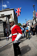 Preparations for the Royal Wedding. Whitehall in central London is now decked out with rows of giant Union Jack flags along the parade route. During the changing of the guard ceremony a Life Guard marches out.