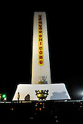 Woman gazes up at the floodlit stone obelisk atop Martyrs' Memorial Hill (Dai Liet Si) at night. Vung Tau, Vietnam