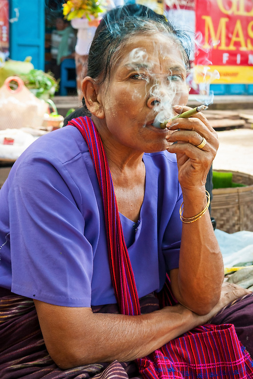 A woman smokes a cheroot while sitting in the market in Kalaw, Myanmar