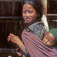 A young Nepali girl carries her brother in a blanket in their village in the Kali Gandaki Valley.