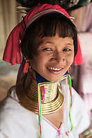 """Karen Hill Tribes living along the border with Myanmar in Thailand, The Padaung members of the Burmese Karen are also known as the Padaung or """"long-necks"""" because of the heavy brass rings they wear around their necks. How they came to be """"long-necks"""" is the stuff of legend. Long ago, the headman of the tribe had a dream in which he was told that a tiger was going to kill one of the children in the village, a child that had been born on a Wednesday.  Since tigers kill their victims by first breaking their necks, the headman decreed that all children born on a Wednesday should wear heavy brass rings round their necks."""