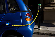 A power cable plugs into the place of a petrol cap while recharging G-Wiz car in central London. A power cable plugs into the place of a petrol cap while recharging a G-Wiz AEV (Automatic Electric Vehicle) car. The car is parked at the kerbside in Dover Street and is hooked up to a recharging point. The AEV has a range of up to 48 miles per charge with a certified top speed of 50 mph. A charging station, also called an electric recharging point and EVSE (Electric Vehicle Supply Equipment) supplies electricity for the recharging of electric vehicles (including plug-in hybrids). Although most electric cars can be recharged from a domestic wall socket, many support faster charging at higher voltages and currents that require dedicated equipment with a specialized connector.