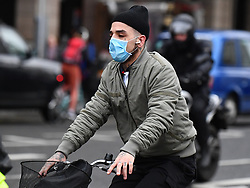 © Licensed to London News Pictures. 10/03/2020. London, UK. A member of the public riding a bike while wearing a medical mask on Westminster Bridge in central London. New cases of the COVID-19 strain of Coronavirus are being reported daily as the government outlines it's plans for controlling the outbreak. Photo credit: Ben Cawthra/LNP