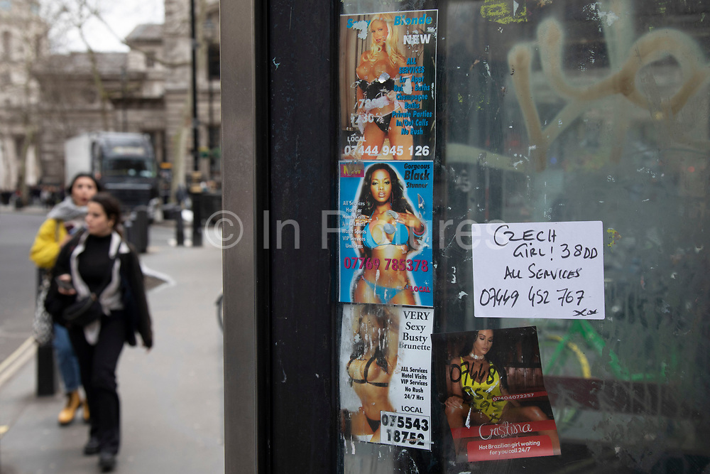 People passing a public telephone box which has sex cards tacked up inside on 18th February 2020 in London, England, United Kingdom. These advertising cards for prostitutes are how people advertise for sexual services under the guise of other services like massage for example.