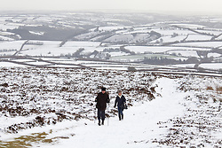 © Licensed to London News Pictures. 14/01/2015. Wheddon Cross, Devon, UK. Two walkers on Dunkery Hill in Exmoor National Park, Devon this morning, 14th January 2015. Snow has fallen overnight across many parts of England, causing travel disruption in some areas.  Photo credit : Rob Arnold/LNP