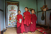 Young Buddhist monks in their room,  at Nalanda Buddhist Monastery, Punakha, Bhutan..Bhutan the country that prides itself on the development of 'Gross National Happiness' rather than GNP. This attitude pervades education, government, proclamations by royalty and politicians alike, and in the daily life of Bhutanese people. Strong adherence and respect for a royal family and Buddhism, mean the people generally follow what they are told and taught. There are of course contradictions between the modern and tradional world more often seen in urban rather than rural contexts. Phallic images of huge penises adorn the traditional homes, surrounded by animal spirits; Gross National Penis. Slow development, and fending off the modern world, television only introduced ten years ago, the lack of intrusive tourism, as tourists need to pay a daily minimum entry of $250, ecotourism for the rich, leaves a relatively unworldly populace, but with very high literacy, good health service and payments to peasants to not kill wild animals, or misuse forest, enables sustainable development and protects the country's natural heritage. Whilst various hydro-electric schemes, cash crops including apples, pull in import revenue, and Bhutan is helped with aid from the international community. Its population is only a meagre 700,000. Indian and Nepalese workers carry out the menial road and construction work.