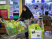 08 JULY 2013 - PATTANI, PATTANI, THAILAND:  A Thai Muslim woman sits with her full shopping carts in a grocery store in Pattani Monday afternoon, the day before Ramadan. Ramadan starts July 9 and Monday was the last day observant Muslims were able to eat and drink during daylight hours. Muslims fast during the holy month of Ramadan, taking breakfast before dawn and not eating again until after sunset. The restaurants in Pattani, a Muslim majority city in southern Thailand, were packed Monday afternoon and evening.   PHOTO BY JACK KURTZ