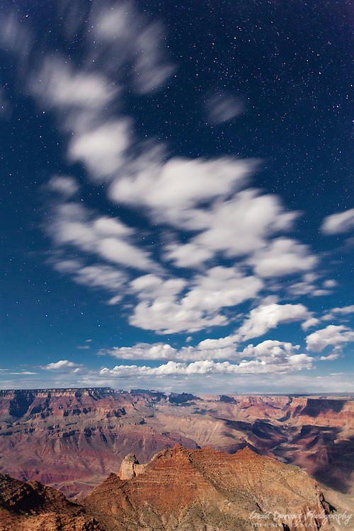 Light clouds and a distant storm over the Grand Canyon on a warm, summer evening.