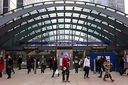 Commuters and city works at the entrance of the iconic Canary Wharf tube station entrance in London, England, Untied Kingdom. Canary Wharf is one of London's financial districts. The station entrance is covered by a large curved glass canopy.