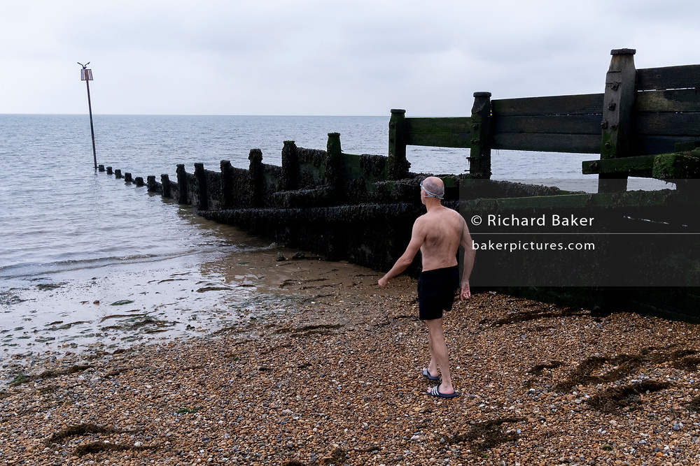 A sea swimmer enters the tidal waters of the Thames Estuary, on 26th July 2021, in Whitstable, England.