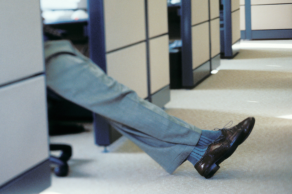 A mans legs stretched out into a hallway from his work cubicle.