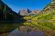 The Maroon Bells reflect in early autumn.