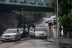 © Licensed to London News Pictures. 23/06/2016. London, UK. As rainwater collects under the railway bridge on the Rickmansworth Road, some cars which tried to drive through have their engines flooded.  A torrential rain shower lasting for more than 30 minutes causes localised flooding in Northwood, north west London. Photo credit : Stephen Chung/LNP